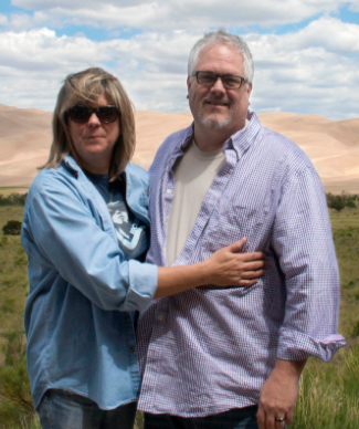 Patients Joe and Becky L. standing in front of sand dunes and smiling